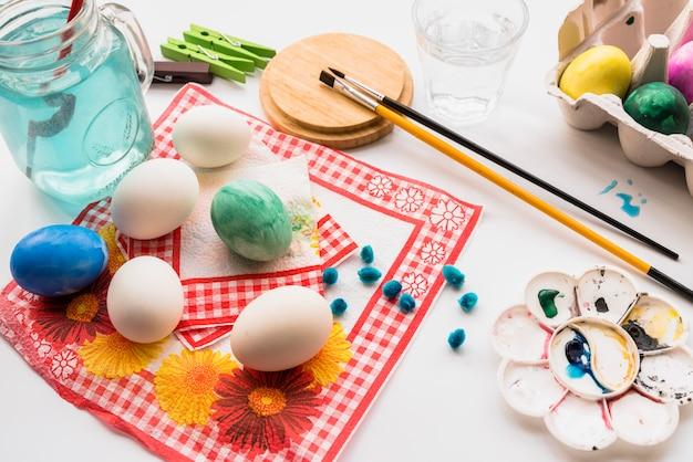 Concept de coloration des œufs sur des serviettes près de la palette et des pinceaux Photo gratuit