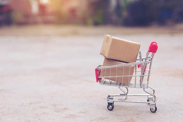 Concept commercial: cartons ou boîtes de papier dans un panier sur un sol en béton. avec copie sp Photo Premium