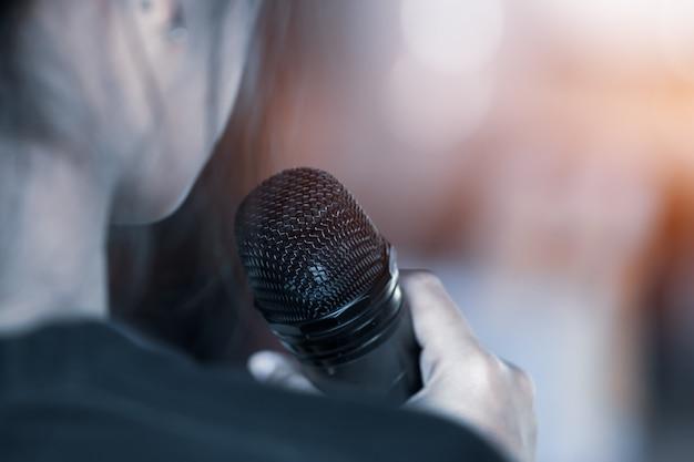 Concept de conférence: verso du discours d'une femme d'affaires intelligente et avec un microphone Photo Premium