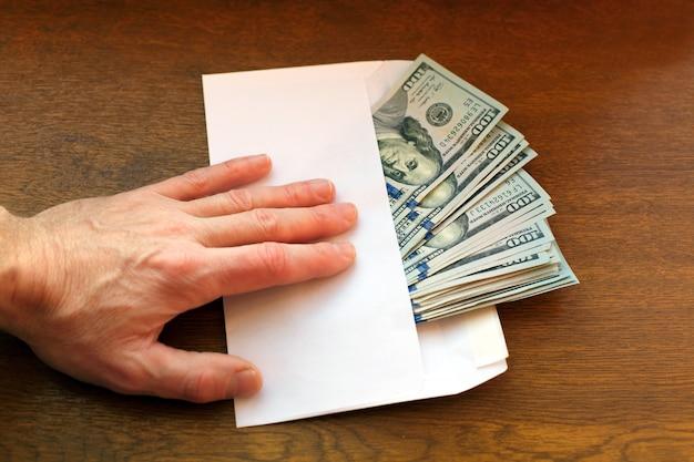 Concept de corruption. homme d'affaires prend une pile d'argent dans une enveloppe. Photo Premium