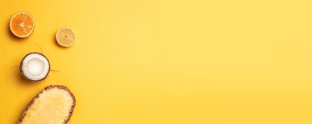 Concept créatif de fruits exotiques: ananas, noix de coco, orange, citron sur fond jaune. pose à plat Photo Premium