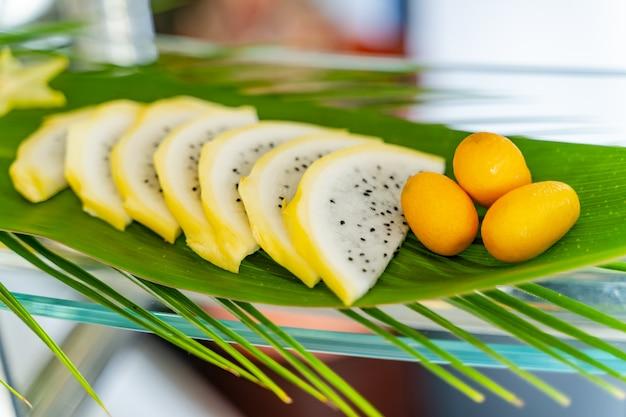 Concept créatif avec des fruits exotiques tranchés et trois petites oranges sur la feuille verte. fruits exotiques en plein air. fermer Photo Premium