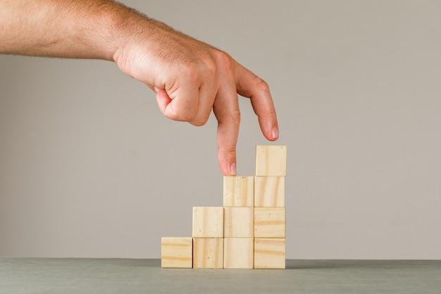 Concept De Croissance D'entreprise Sur La Vue Latérale Du Mur Gris Et Blanc. Homme Mettant Les Doigts Dans Les Escaliers. Photo gratuit