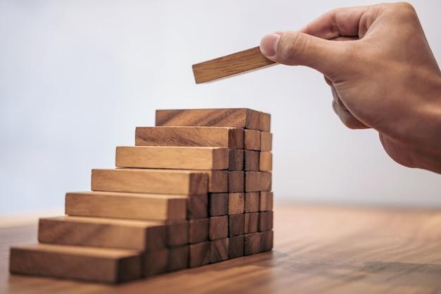 Concept de croissance des entreprises avec des blocs de bois, la main de l'homme a empiler et empiler un woode Photo Premium