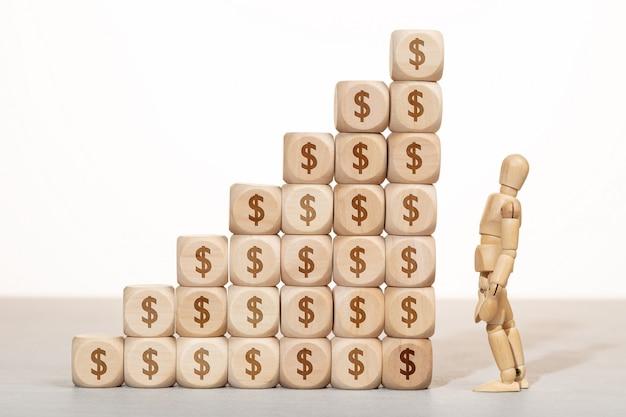 Concept De Croissance, De Richesse Ou De Richesse. Mannequin En Bois à La Recherche D'un Groupe De Blocs En Bois Empilés Avec Symbole Dollar Photo Premium