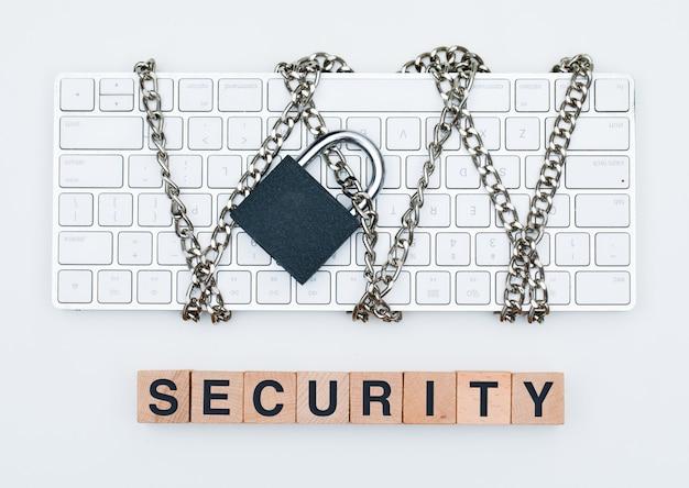 Concept De Cybersécurité Avec Chaîne Et Cadenas Sur Clavier, Cubes En Bois Sur Fond Blanc à Plat. Photo gratuit