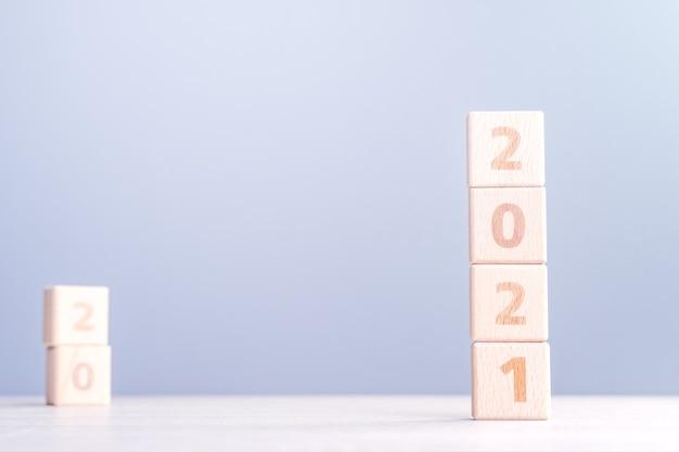 Concept De Design Abstrait De Nouvel An 2021 - Cubes De Bloc De Bois Numéro Isolés Sur Table En Bois Et Fond Bleu Brouillard Léger. Photo Premium