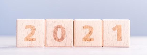 Concept De Design Abstrait De Nouvel An 2021 - Cubes De Bloc De Bois Numéro Isolés Sur Table En Bois Et Fond Bleu Brouillard Léger Photo Premium
