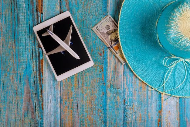 Concept De Dispositifs De Tourisme De Voyage Tablette Tactile Pad Blue Hat Préparation Pour Voyager Des Billets En Dollars Américains Photo Premium