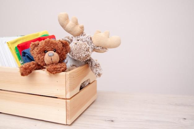 Concept de donation. donnez une boîte avec des vêtements pour enfants, des livres, des fournitures scolaires et des jouets. Photo Premium