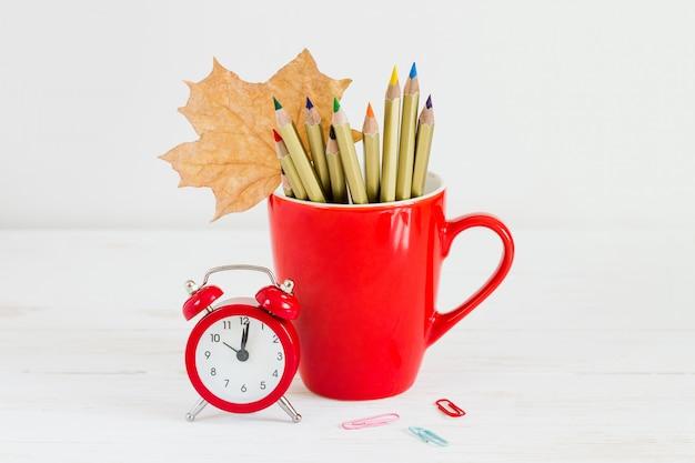 Concept du 1er septembre. réveil rouge, tasse, crayons de couleur et feuille d'érable. concept de retour à l'école Photo Premium