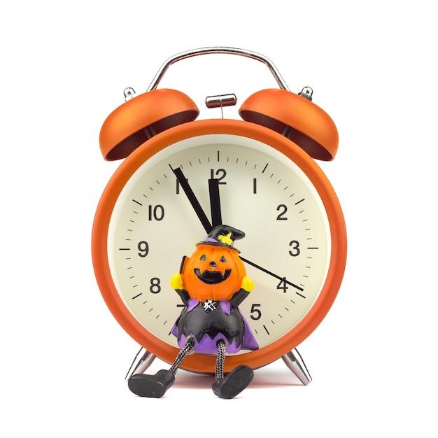 Concept du festival holloween. réveil orange avec jouet fantôme citrouille Photo Premium