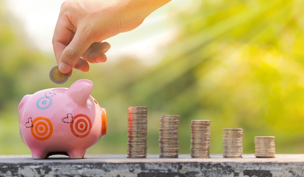 Le concept d'économiser de l'argent, main mettre une pièce de monnaie dans la tirelire sur fond de jardin flou Photo Premium