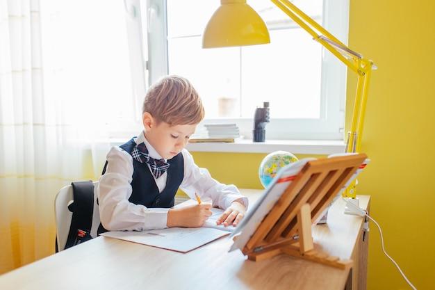 Concept d'éducation à la maison - mignon petit garçon qui étudie ou termine son travail à domicile sur une table d'étude avec une pile de livres, un globe éducatif et un cahier d'exercices Photo Premium