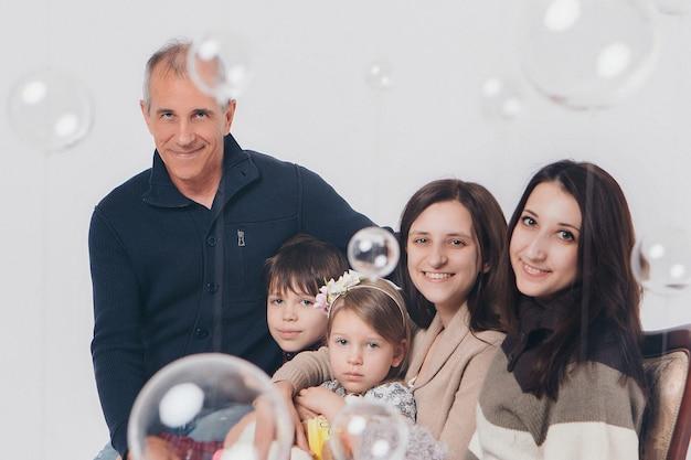 Concept d'enfance heureuse, famille, amour - groupe de personnes sur fond blanc: adultes et enfants avec des jouets assis sur le même canapé Photo Premium