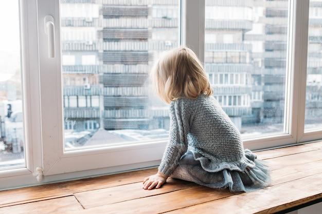 Concept de l'enfance. petite fille assise près de la fenêtre à la maison. Photo Premium