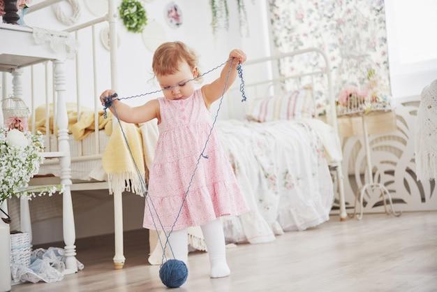 Concept d\'enfance. petite fille en robe mignonne joue avec ...