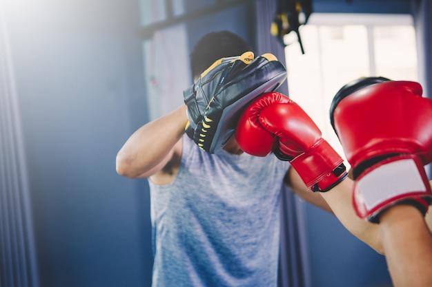 Concept d'entraînement; jeune homme s'entraînant en classe; jeunes pratiquant la boxe et le jeu de jambes en classe d'entraînement Photo Premium