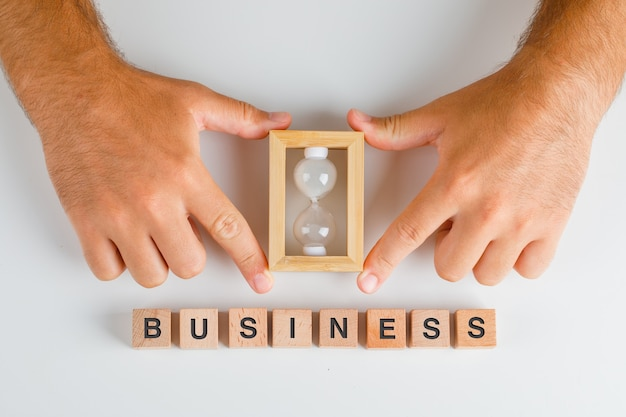 Concept D'entreprise Avec Des Blocs De Bois Sur Table Blanche à Plat. Homme Mains Tenant Sablier. Photo gratuit
