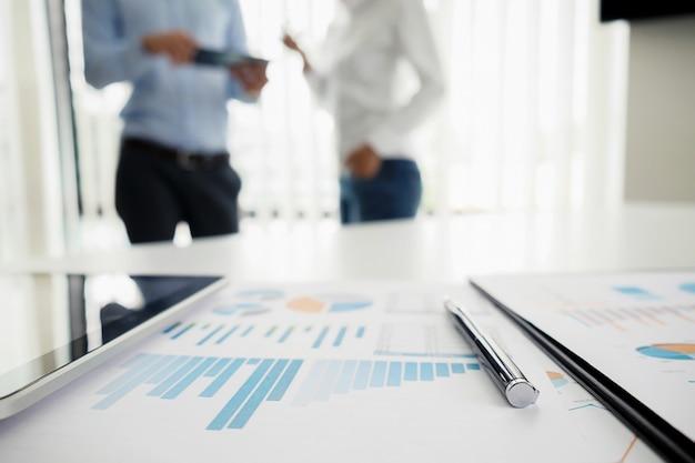 Concept d'entreprise avec copie. table de bureau avec lunettes focus et tableau d'analyse ordinateur ordinateur portable tasse de café sur le bureau. tonalité d'entrée rétro effet de filtre. mise au point sélective. Photo Premium