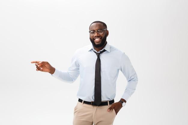 Concept d'entreprise - doigt de pointage jeune afro-américain réfléchie confiant sur le côté sur fond gris. Photo Premium