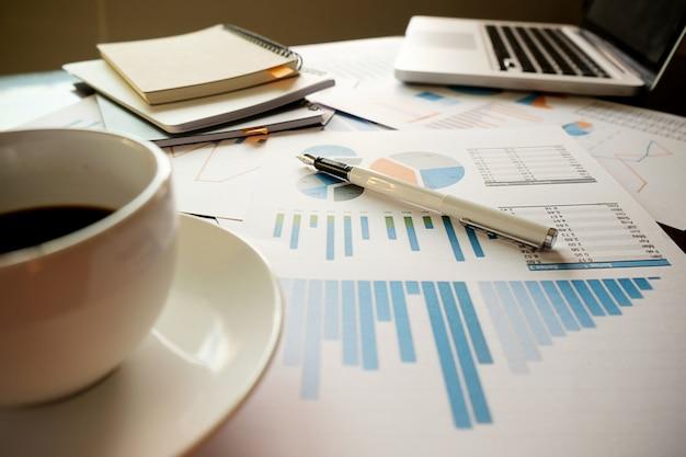Concept d'entreprise avec espace de copie. table de bureau avec stylo et tableau d'analyse, ordinateur, ordinateur portable, tasse de café sur le bureau. tonalité de rétro filtre rétro, mise au point sélective. Photo gratuit