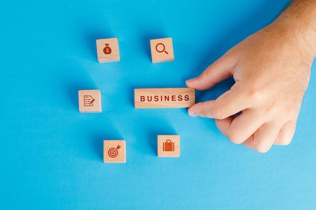 Concept D'entreprise Avec Des Icônes Sur Des Cubes En Bois Sur Table Bleue à Plat. Main Tenant Un Bloc De Bois. Photo gratuit