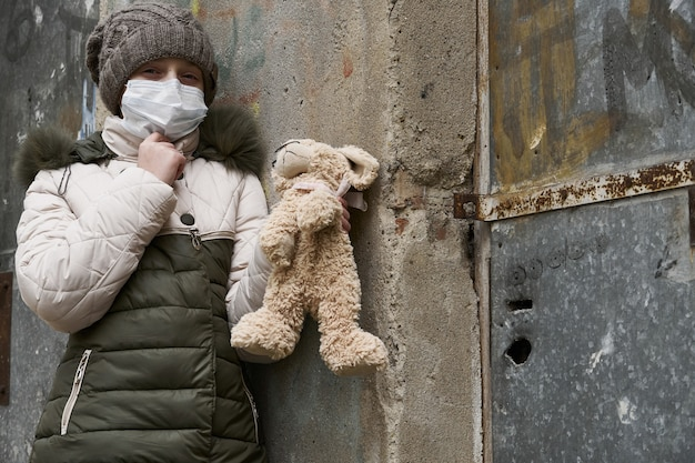 Concept D'épidémie Et De Quarantaine - Une Fille Avec Un Masque Facial Et Une Peluche Seule Dans La Rue De La Ville Photo Premium