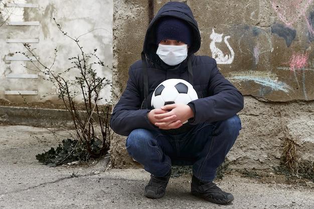 Concept D'épidémie Et De Quarantaine - Un Garçon Avec Un Masque Facial Et Un Ballon Seul Dans La Rue De La Ville Photo Premium