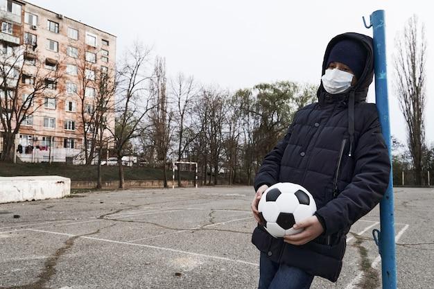 Concept D'épidémie Et De Quarantaine - Un Garçon Avec Un Masque Facial Et Un Ballon Seul Sur La Zone Sportive De La Ville Photo Premium