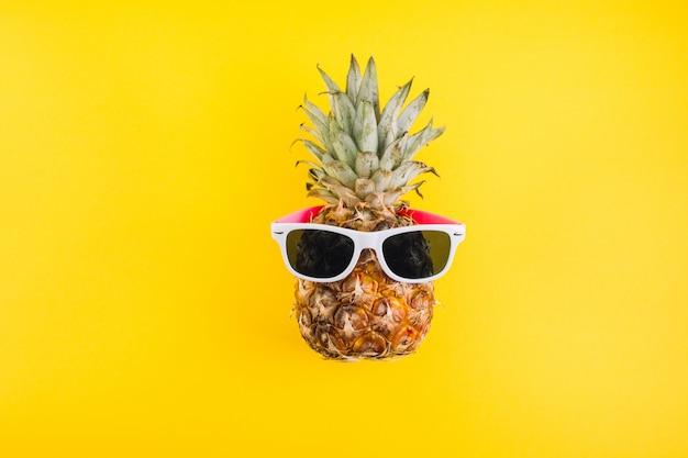 Concept de l'été. ananas mignon et drôle avec des lunettes de soleil sur fond jaune. Photo Premium