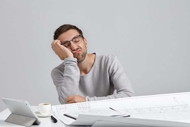 Concept De Fatigue. Concepteur Ou Ingénieur Masculin Barbu Endormi épuisé Se Penche à Portée De Main Photo gratuit