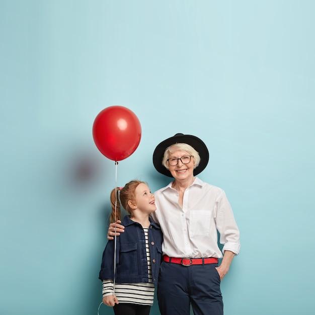 Concept De Fête De Famille. Jolie Fille Aux Cheveux Rouges Félicite Mamie Mature Avec La Fête Des Mères, Tient Le Ballon à Air Rouge, Embrasse Ensemble, Isolé Sur Un Mur Bleu Avec Un Espace Vide. Photo gratuit