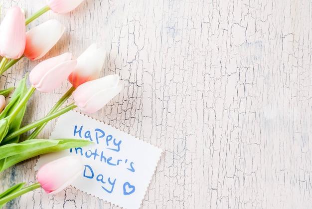 Concept de fête des mères, fond de carte de voeux. fleurs de tulipes et mot de voeux bonne fête des mères Photo Premium