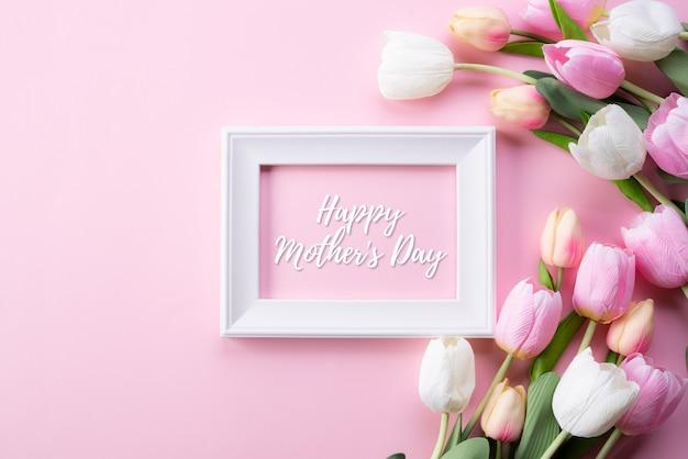 Concept de fête des mères heureux. vue de dessus de la tulipe rose et cadre photo Photo Premium