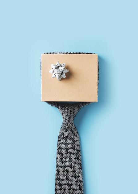 Concept de fête des pères avec boîte-cadeau et cravate sur fond bleu Photo Premium