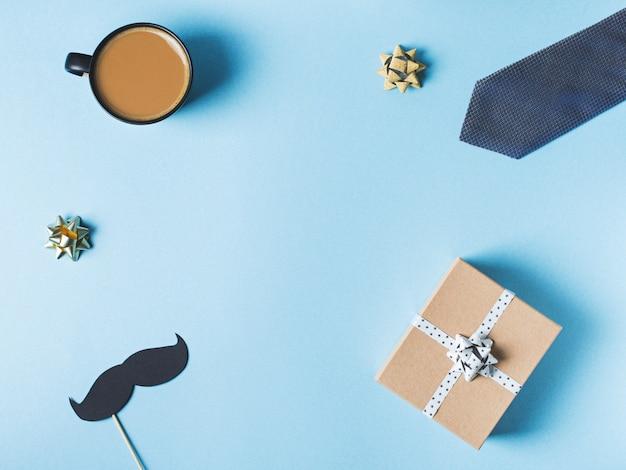 Concept de fête des pères avec boîte-cadeau, cravate et moustache sur fond bleu Photo Premium