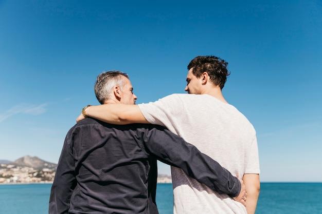 Concept de fête des pères avec père et fils en face de la mer Photo gratuit