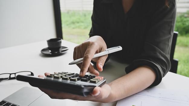 Concept de la finance, données de calcul de femme calcul sur tableau. Photo Premium