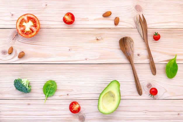 Concept de fond de nourriture et de salade avec des matières premières à plat poser sur fond en bois blanc Photo Premium