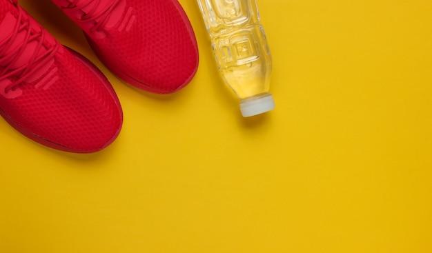 Concept De Formation. Chaussures De Sport, Bouteille D'eau Sur Fond Jaune. Style Plat. Copier L'espace Photo Premium