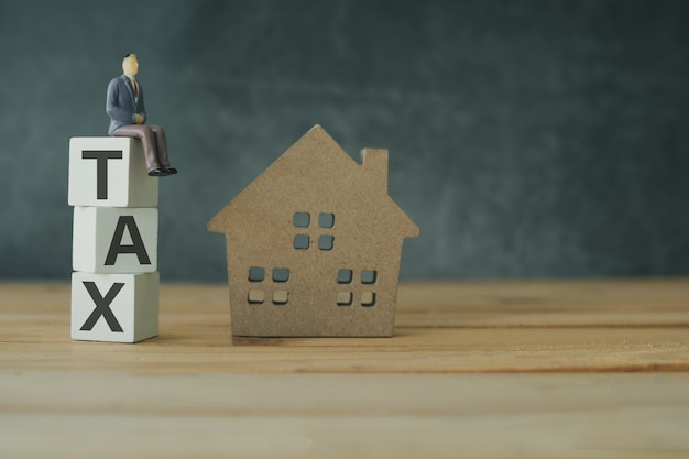 Concept De Gestion De La Taxe Sur L'immobilier, Taxe Sur Le Bois Empilé Avec Modèle De Maison Photo Premium