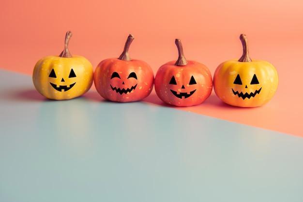 Concept D'halloween, Quatre Citrouilles Avec Sourire Visage Sur Fond De Couleurs Pastel. Photo Premium