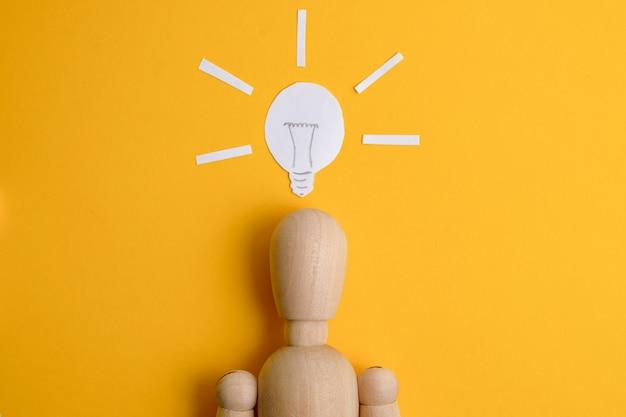 Le concept d'une idée d'entreprise trouvée ou de démarrage. mannequin en bois sur fond jaune sous une ampoule peinte. Photo Premium