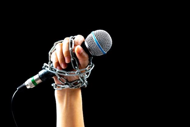 Concept de la journée mondiale de la liberté de la presse. main de femme avec microphone attaché avec une chaîne Photo Premium