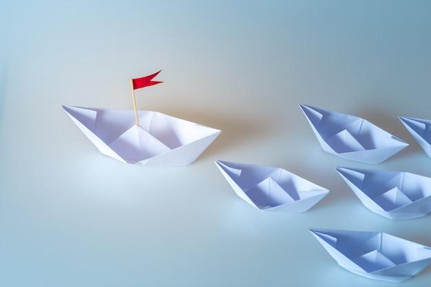 Concept de leadership à l'aide de papier expédier avec drapeau rouge sur fond bleu Photo Premium