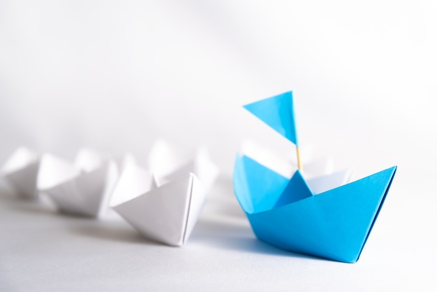 Concept De Leadership. Navire De Papier Bleu Avec Le Drapeau Du Plomb Parmi Les Blancs. Photo Premium