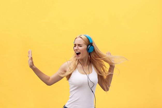 Concept lifestyle: portrait d'une femme joyeuse en t-shirt blanc et écoutant de la musique Photo Premium
