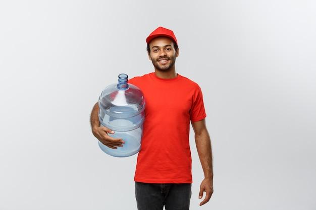 Concept de livraison - handsome african american delivery man tenant un réservoir d'eau. isolé sur fond de studio gris. espace de copie. Photo gratuit