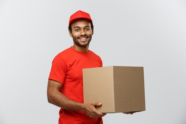Concept De Livraison - Portrait De L'homme De Livraison Happy African American En Tissu Rouge Tenant Un Paquet De Boîte. Isolé Sur Fond De Studio Gris. Espace De Copie. Photo gratuit